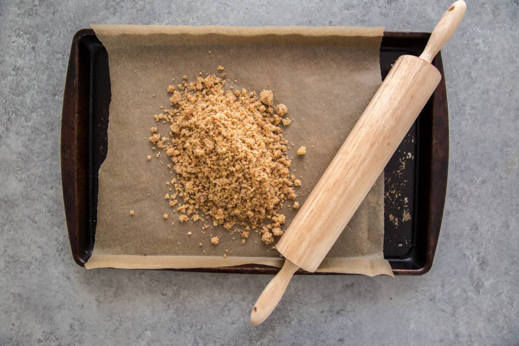 Graham cracker crumbs on a baking tray with a rolling pin