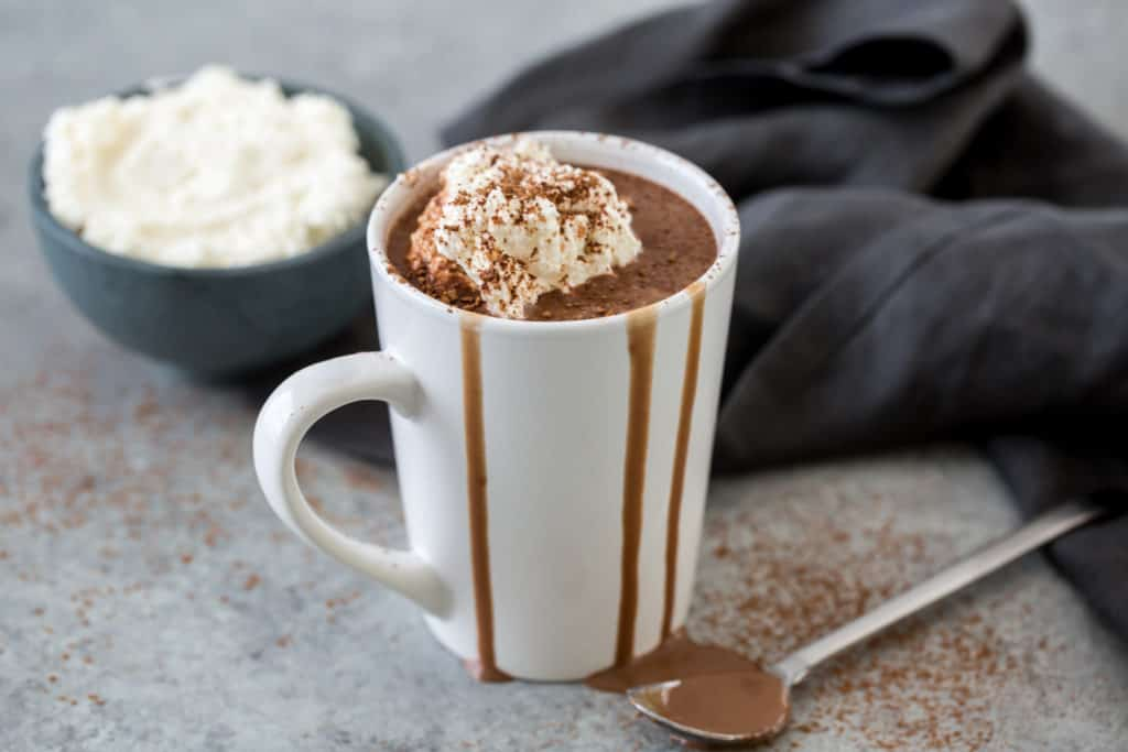 keto hot chocolate in a white mug topped with sugar free whip cream and cocoa powder