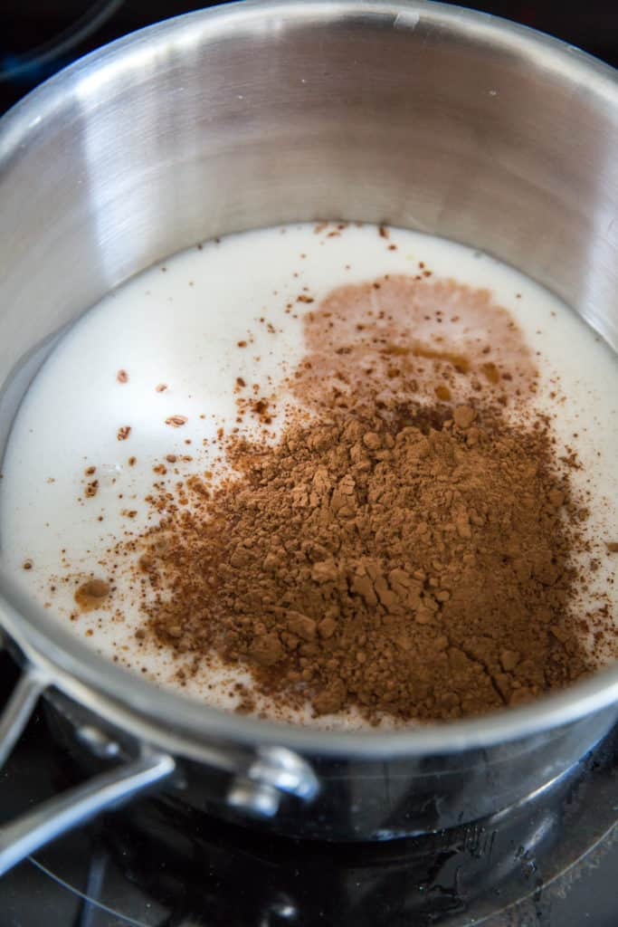a saucepan filled with canned coconut milk and cocoa powder on the stove