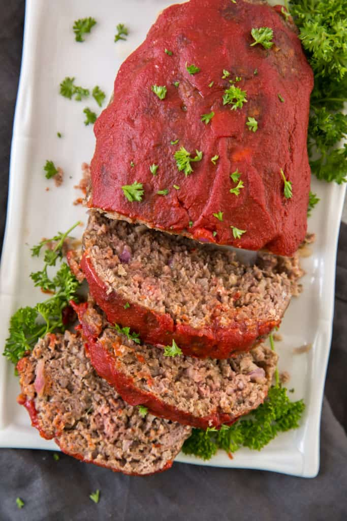 a cooked easy keto meatloaf served on a white platter garnished with parsley and sliced