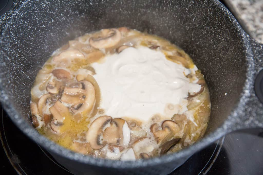 keto beef stroganoff cooking in a skillet with sour cream, mushrooms, onions and beef broth