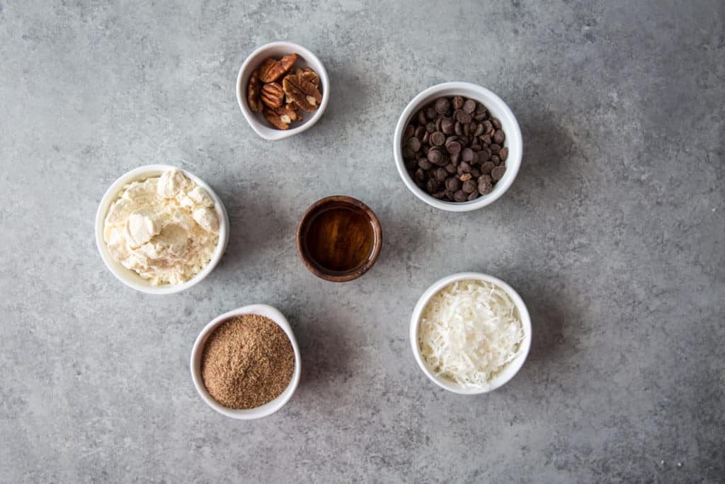 six ingredients to make keto energy balls in small bowls