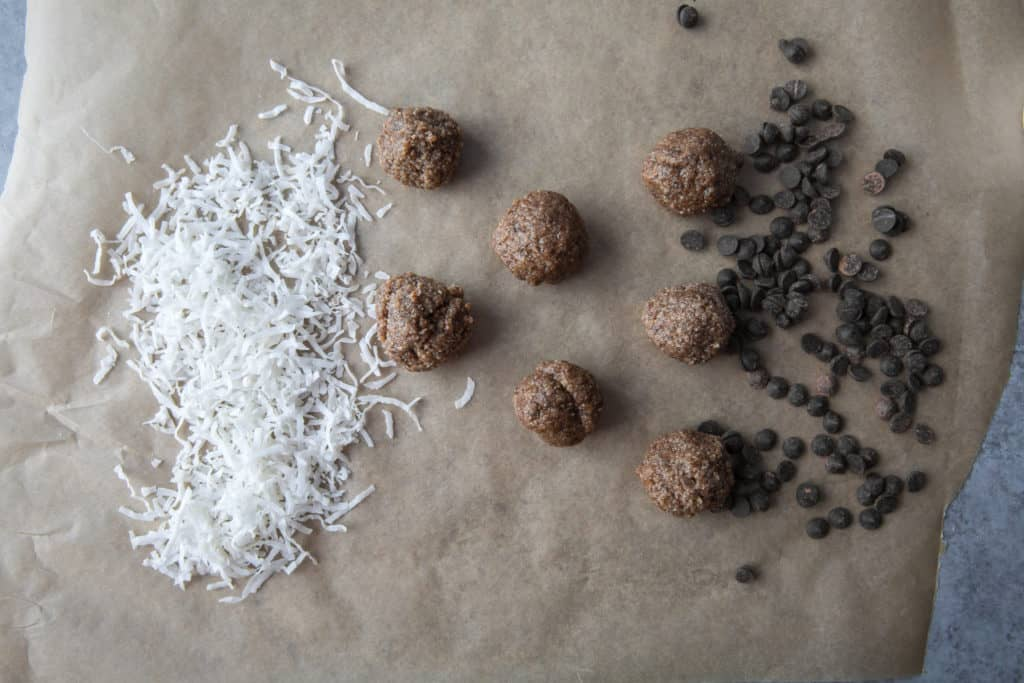 keto energy balls on parchment paper with coconut flakes and low carb chocolate chips