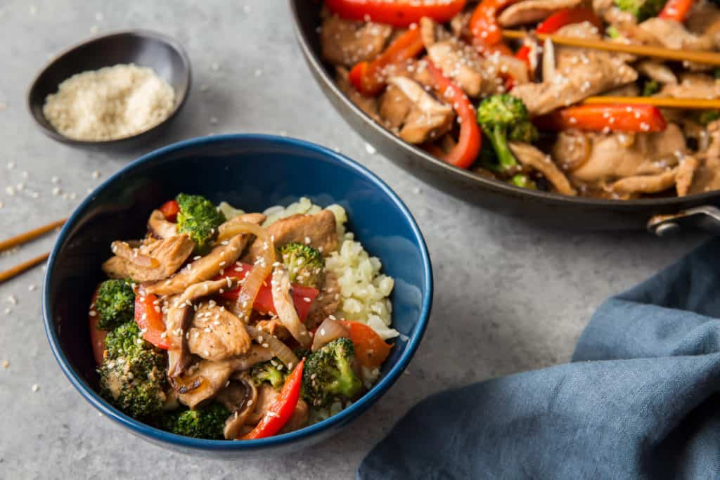 keto chicken stir fry served in a bowl over cauliflower rice