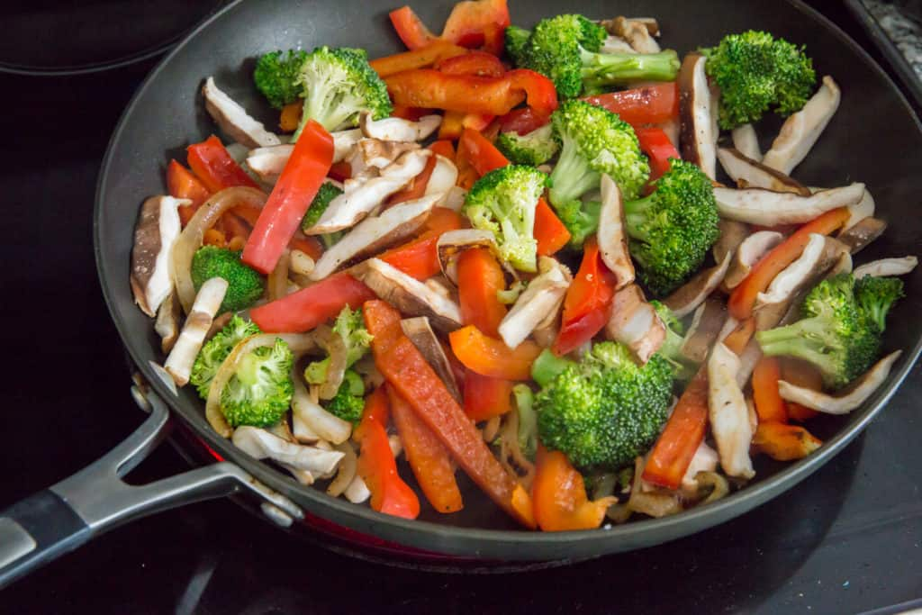 keto chicken stir fry vegetables being cooked in a cast iron skillet prior to adding chicken