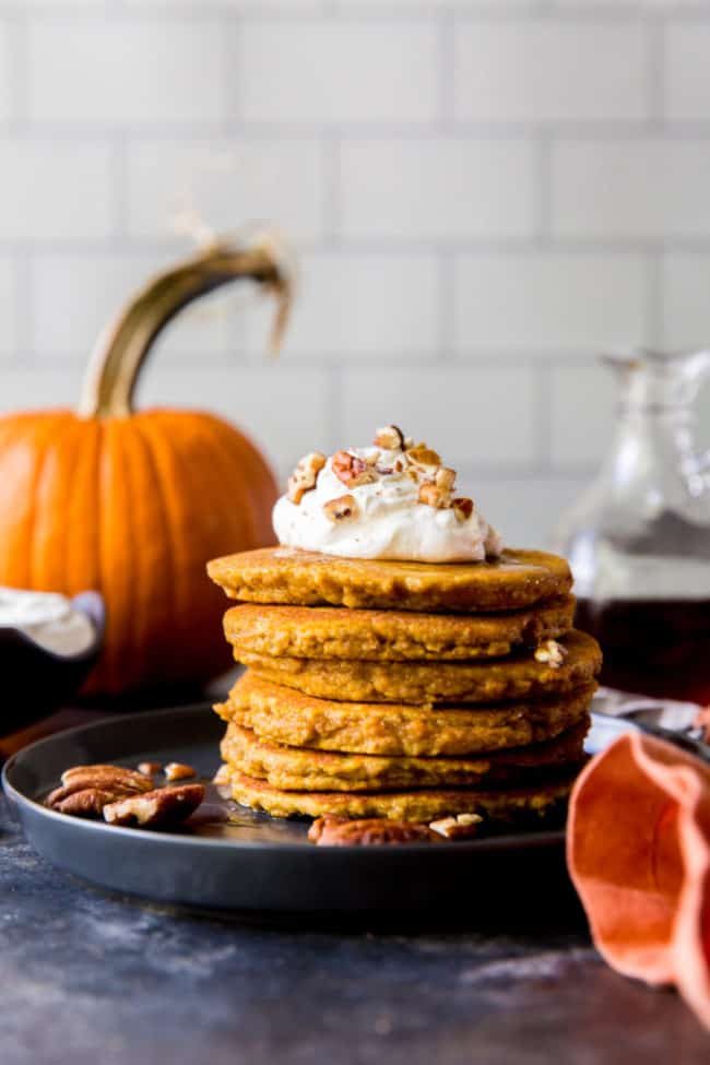 plate of pancakes with toppings and pumpkin in the background