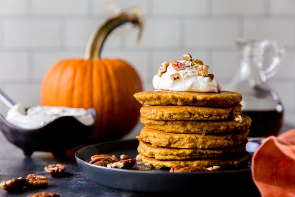 pancakes stacked with whipped cream and pumpkin in the background