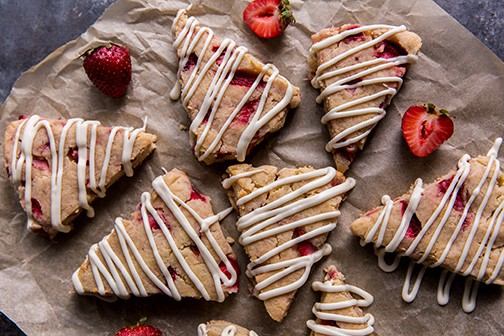 finished pastries with strawberries on parchment paper