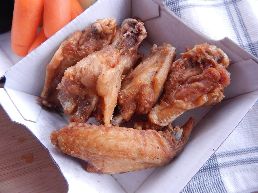 Takeout dry rubbed chicken wings on table