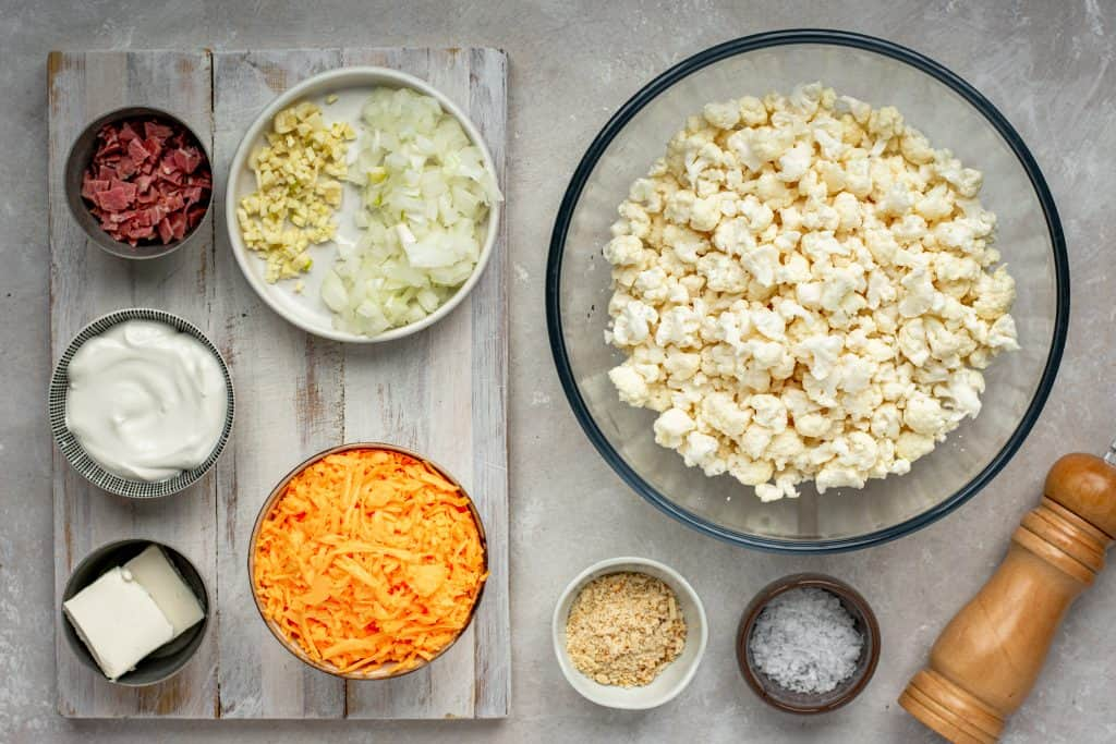 All the ingredients for Keto Mac and Cheese in bowls on a grey wood cutting board