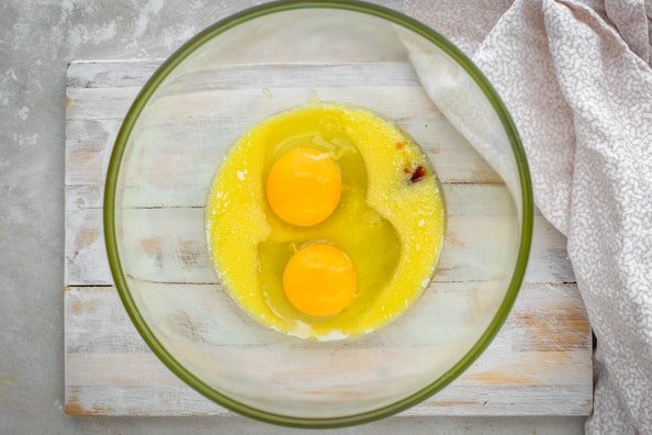 Eggs, butter, and vanilla extract in a glass bowl.