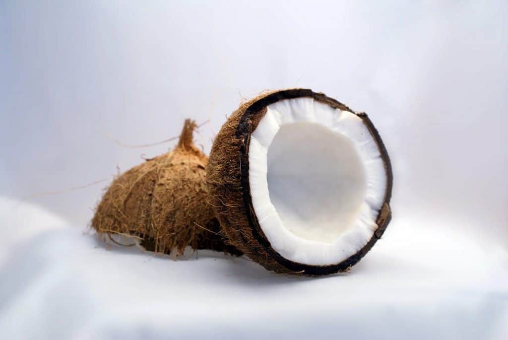 a coconut broken in half on top of sand
