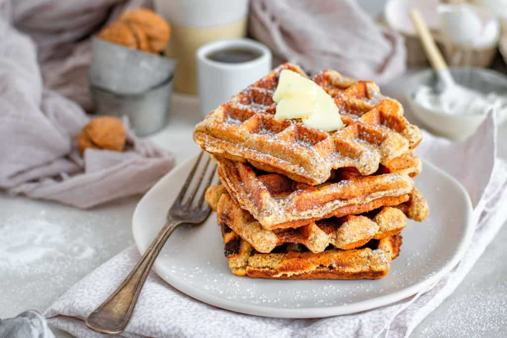 Fluffy keto waffles on a white plate by a dull silver fork.