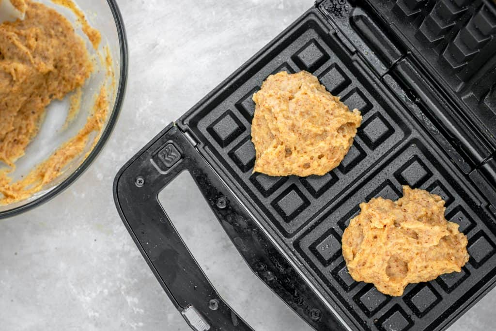 Waffle batter scooped into two square waffle maker sections