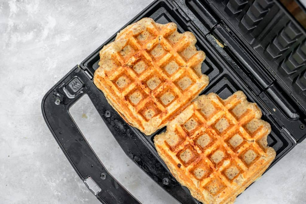 Golden cooked keto waffles in the waffle iron.