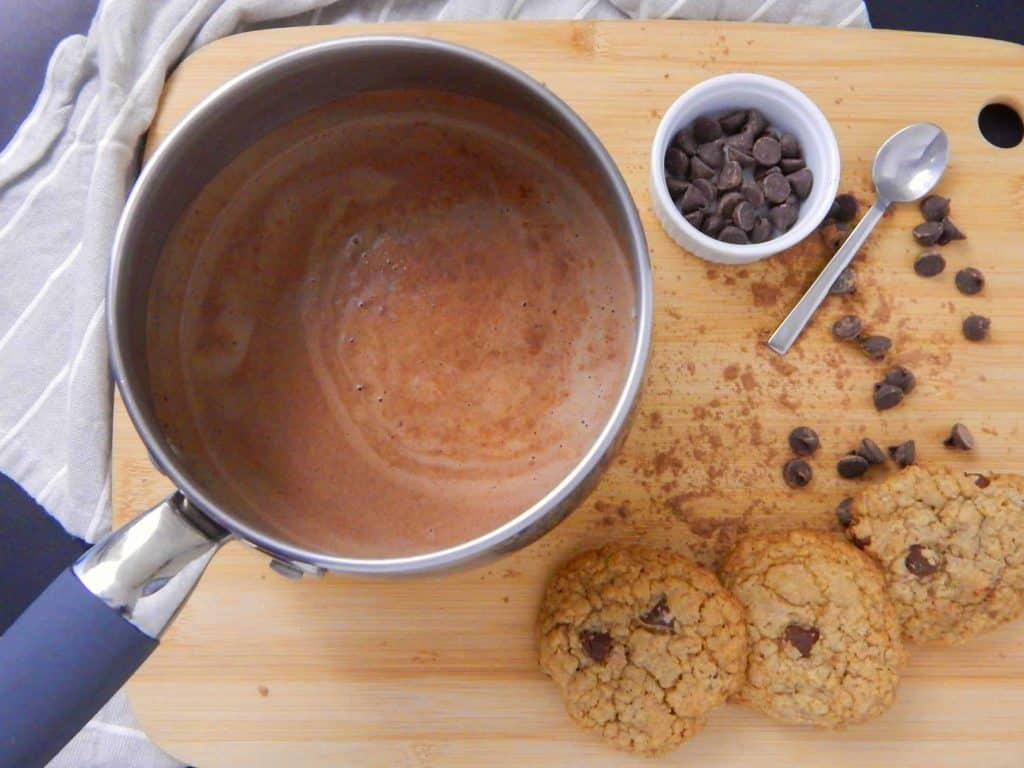 A silver saucepot of hot cocoa next to cookies and chocolate chips.