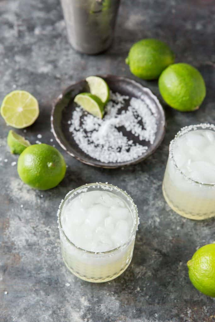 Two completed margaritas in front of a plate with salt and lime wedges.