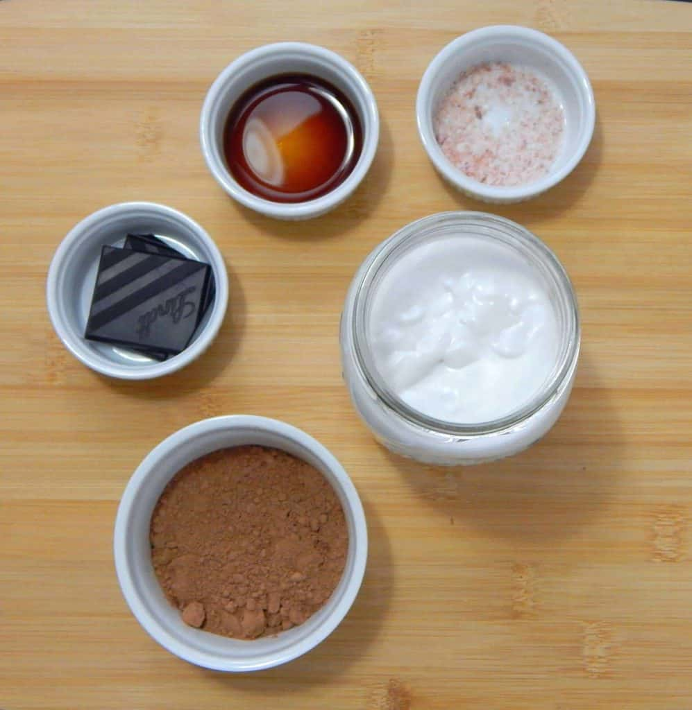 Ingredients for hot chocolate in ceramic dishes on a cutting board.