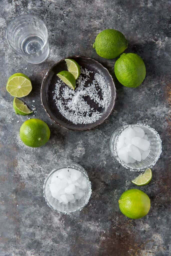 Margarita glasses with salt and ice next to fresh limes