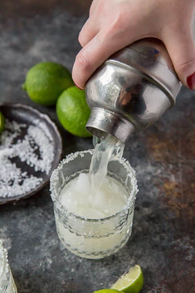 A margarita being poured from a silver cocktail shaker.