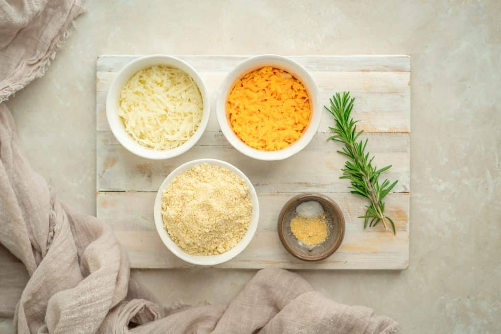 Ingredients for the cheddar crackers on a white wood cutting board