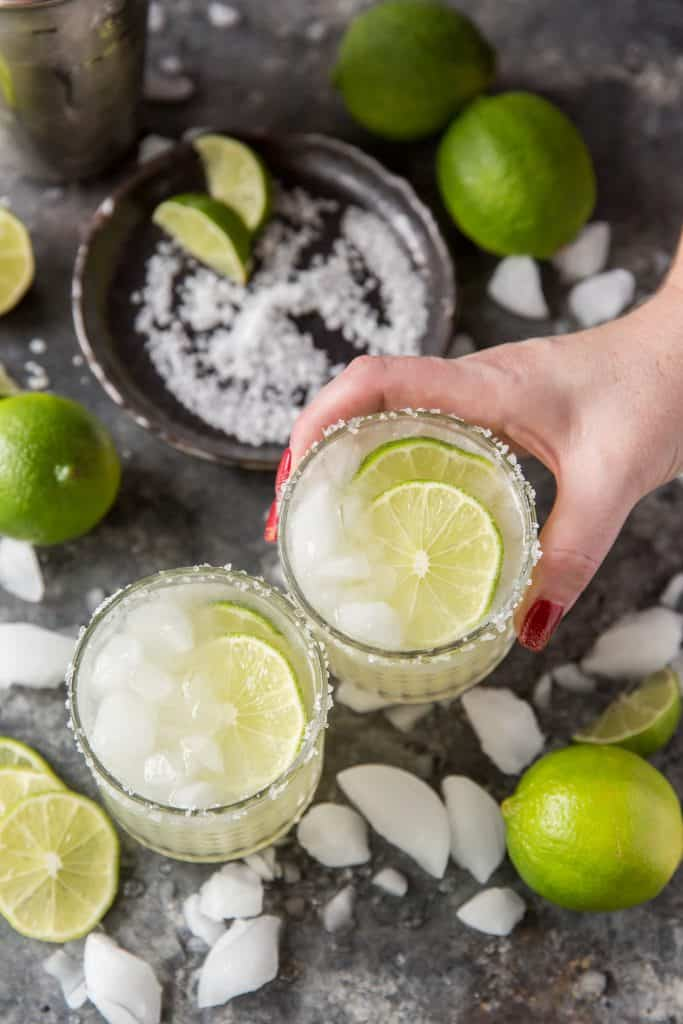 Someone holding a cold keto margarita and clinking glasses.