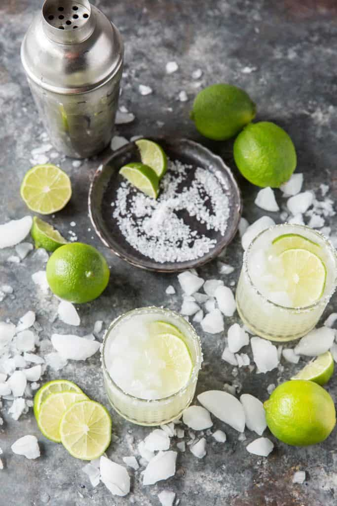 Two Keto Margaritas in glasses topped with lime slices and salt.