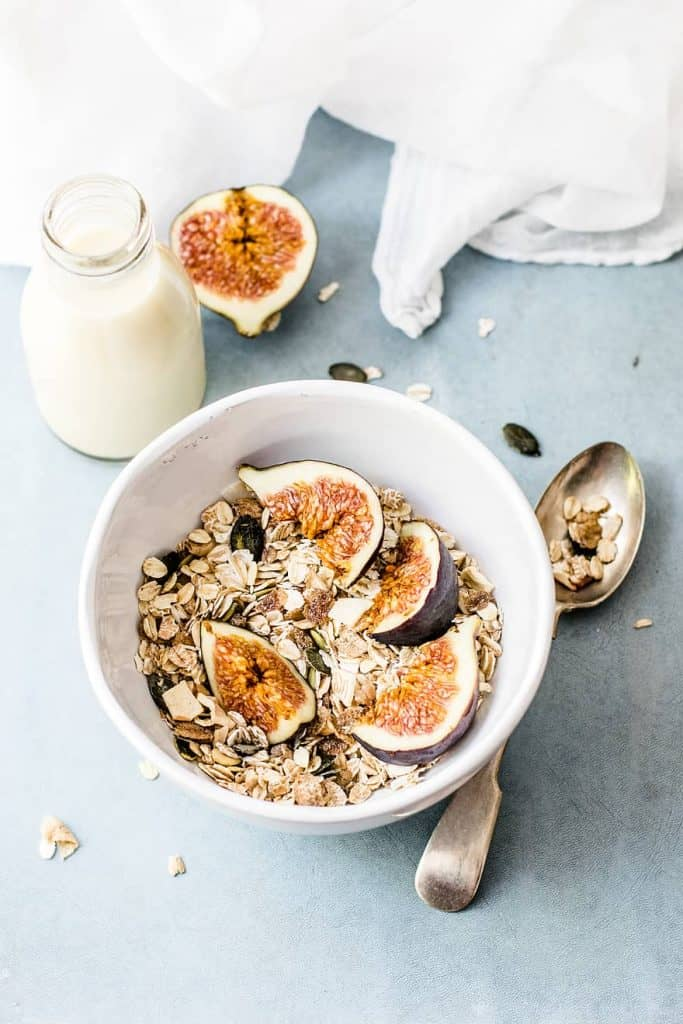 A bowl of granola next to milk and a silver spoon