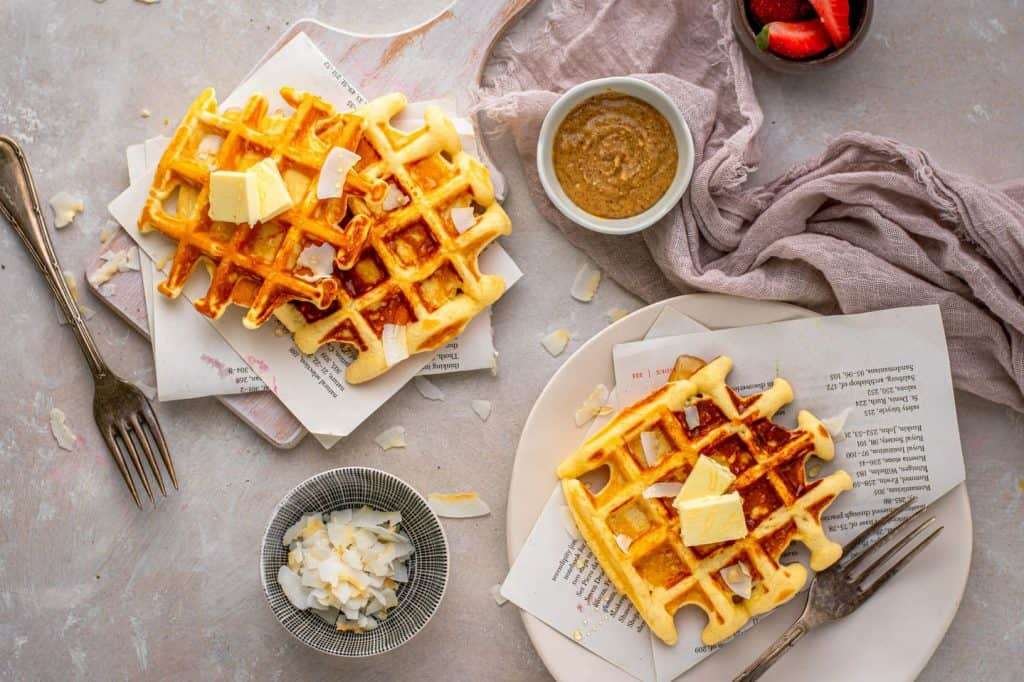 Protein waffles topped with coconut, almond butter, and butter