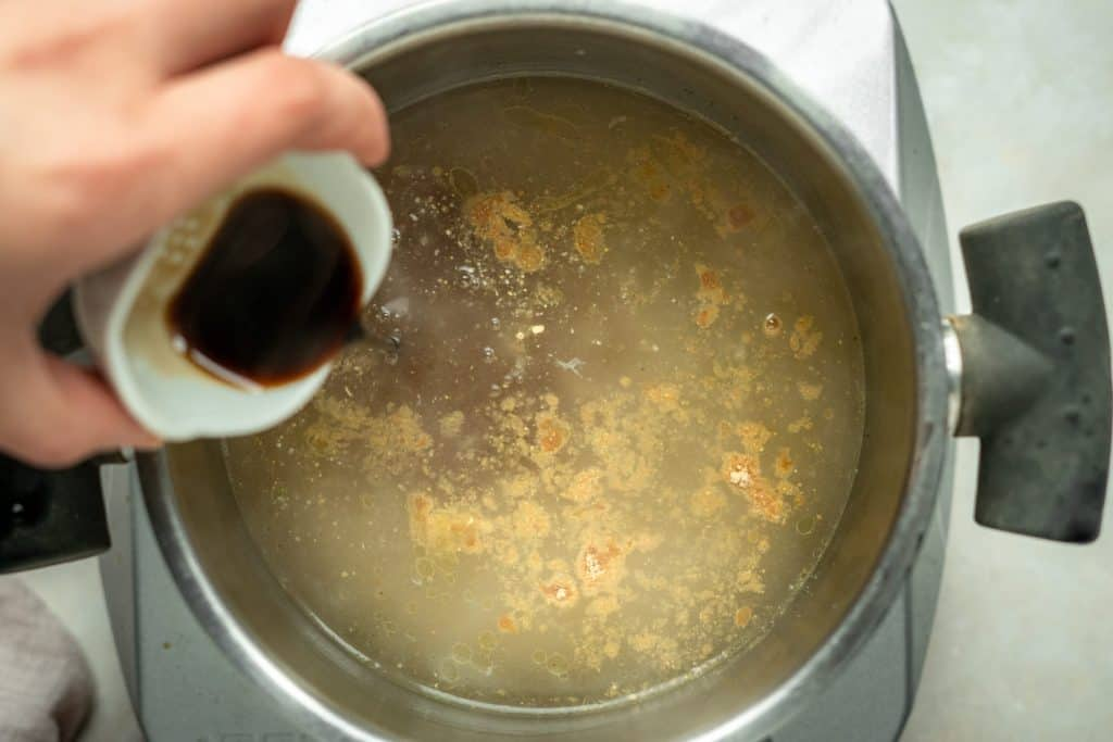 hand mixing spices and soy sauce into chicken broth