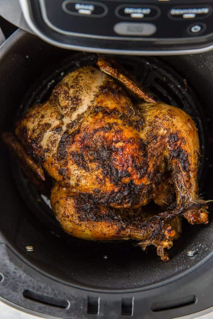 A whole roasted chicken with its legs tied together