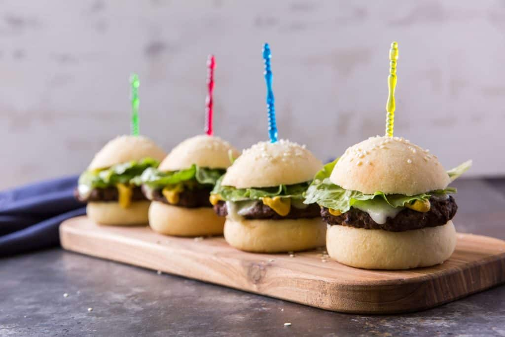 four keto hamburger buns with toothpicks and sesame seeds