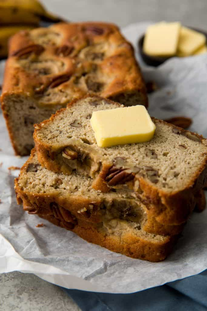 A pat of butter on top of three slices of banana bread