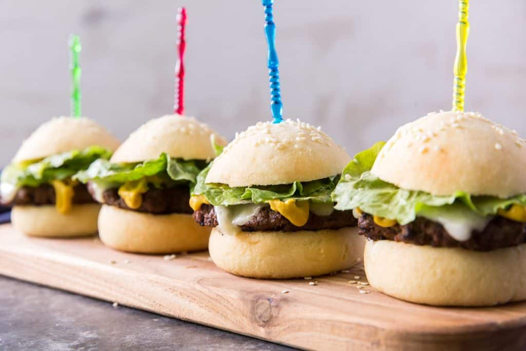 Four sliders on a cutting board sprinkled with sesame seeds