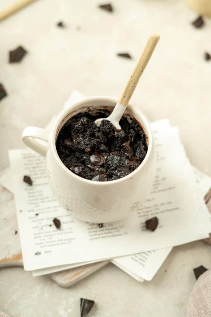 a mug brownie with lots of chocolate chunks around it.