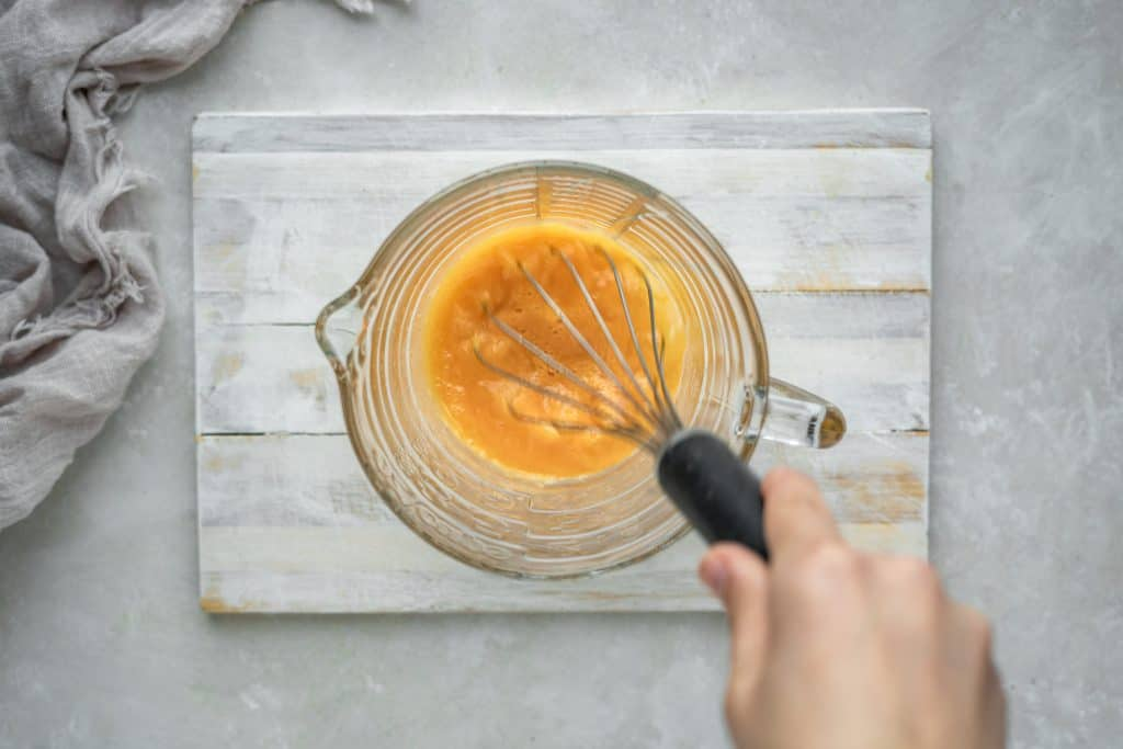 A hand whisking egg yolks in a large glass measuring cup