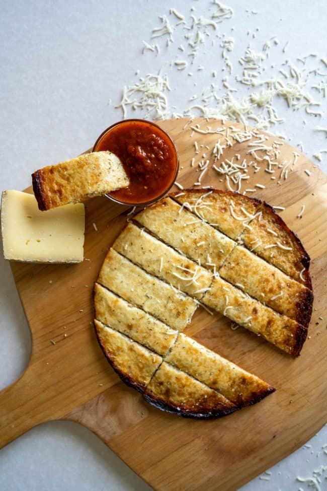 cauliflower breadsticks on a pizza board with marinara dipping sauce