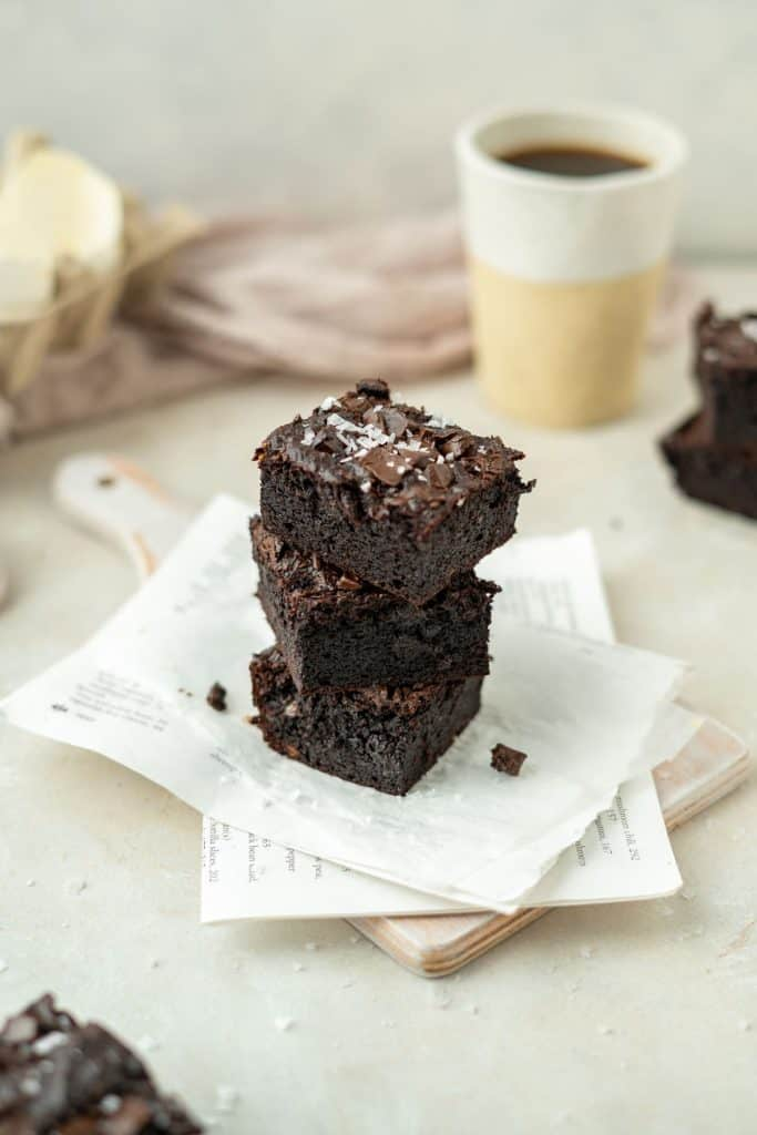 Three brownies stacked with a cup of coffee nearby.