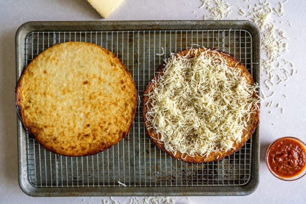 two crusts on a baking tray one with cheese