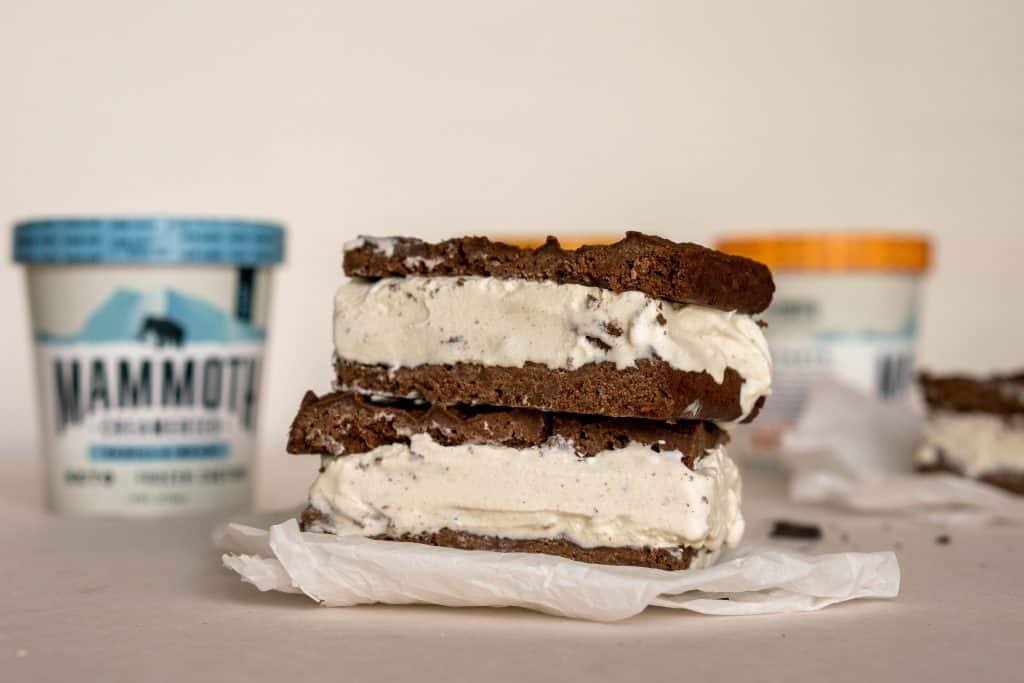two ice cream sandwiches on top of each other with ice cream pints in the background