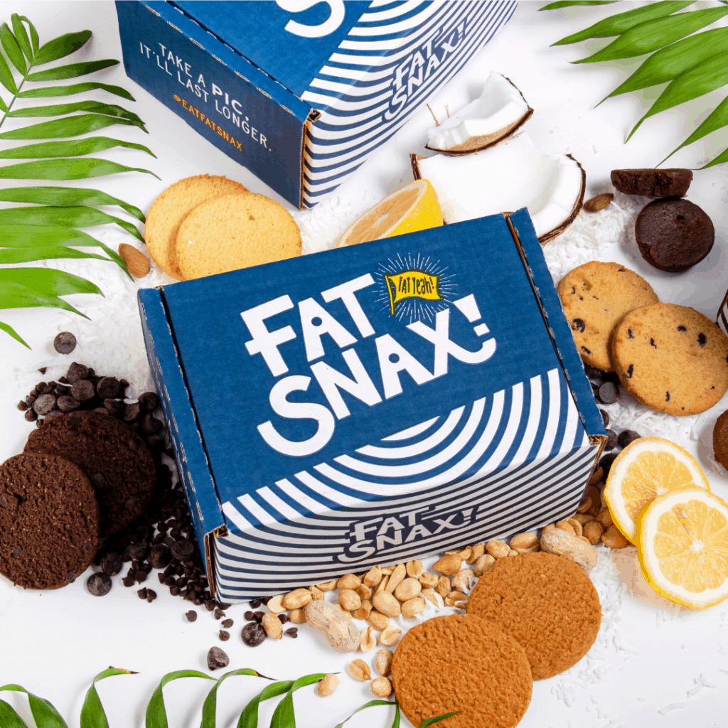 A big box of Fat Snax cookies surrounded by cookies, chocolate chips, peanuts, coconut, and lemon slices