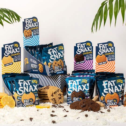 Tropical setting of four packages of fat snax cookies on a bed of coconut