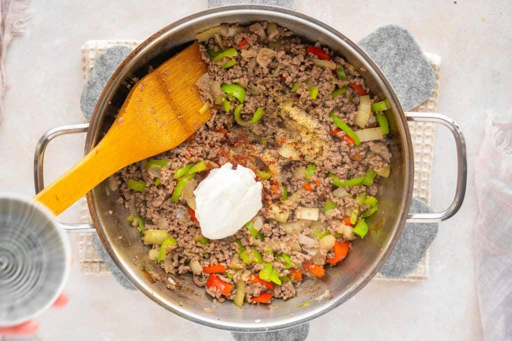 seasonings and cream cheese in ground beef