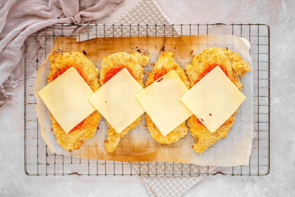 adding cheese on top of the marinara sauce