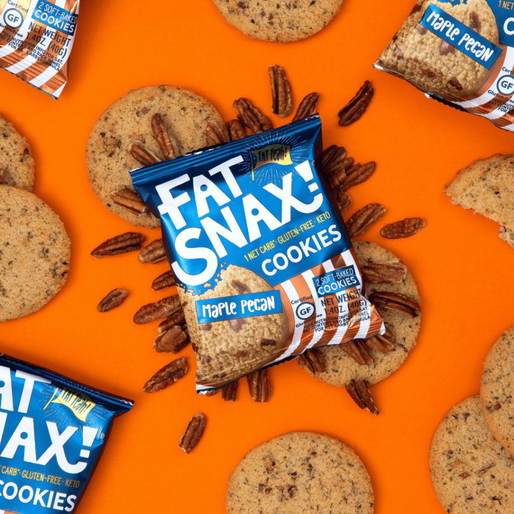 An overhead view of a bag of Fat Snax cookies sitting on top of pecans and cookies
