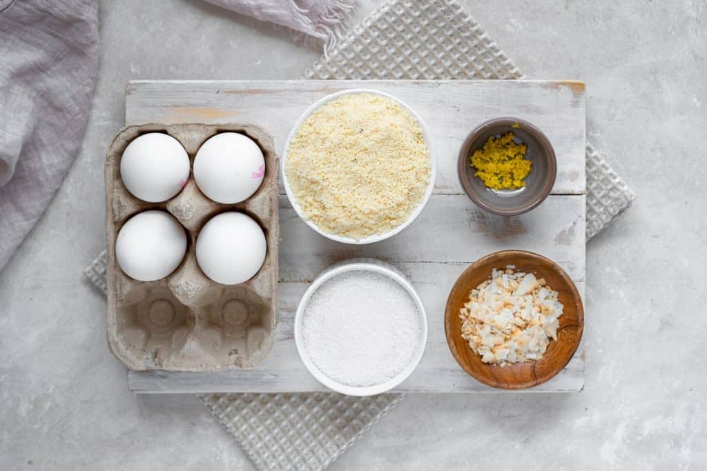Ingredients for almond cake set out in separate bowls. Eggs, almond flour, erythritol, lemon zest, and sliced almonds