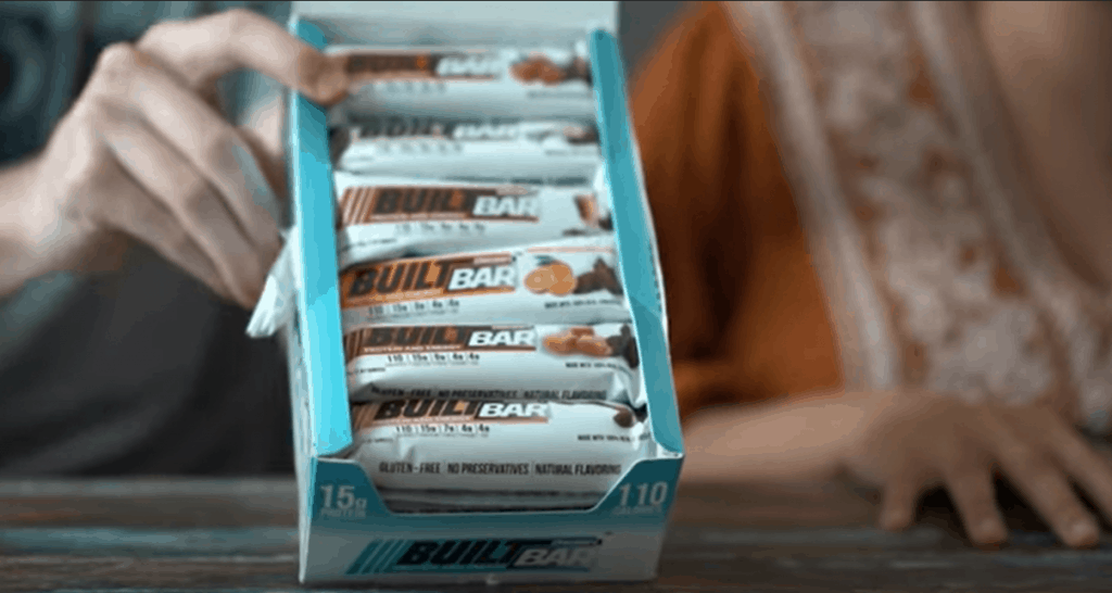 A package of several flavors of Built bars being held up at a 45 degree angle.