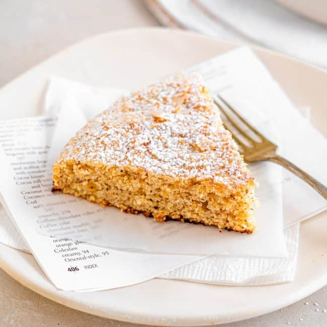 A single piece of Almond Cake sitting on a plate with a fork next to it.