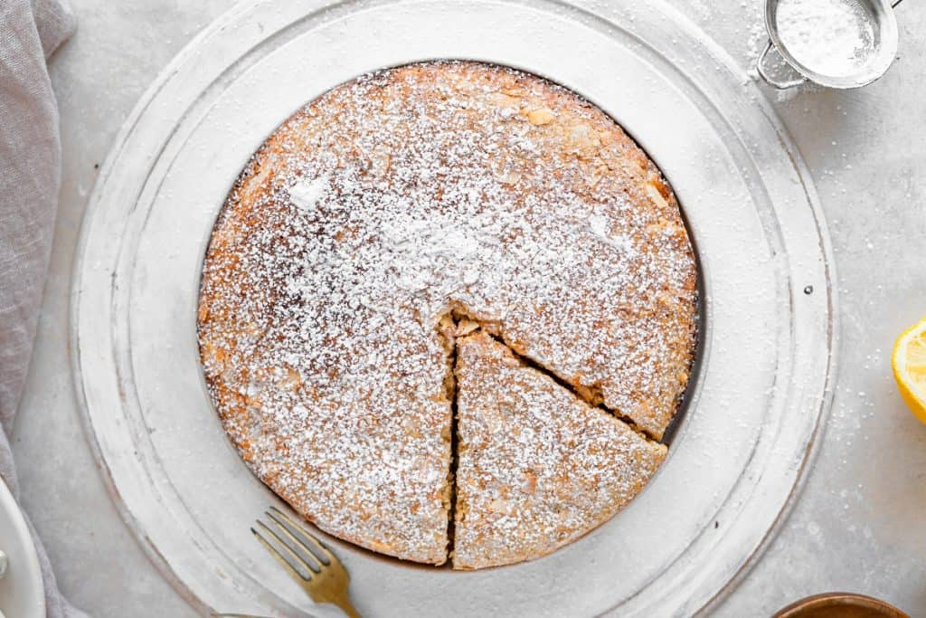 A whole almond cake on a white serving tray with a piece cut out. Lemon and powdered sugar duster next to it.