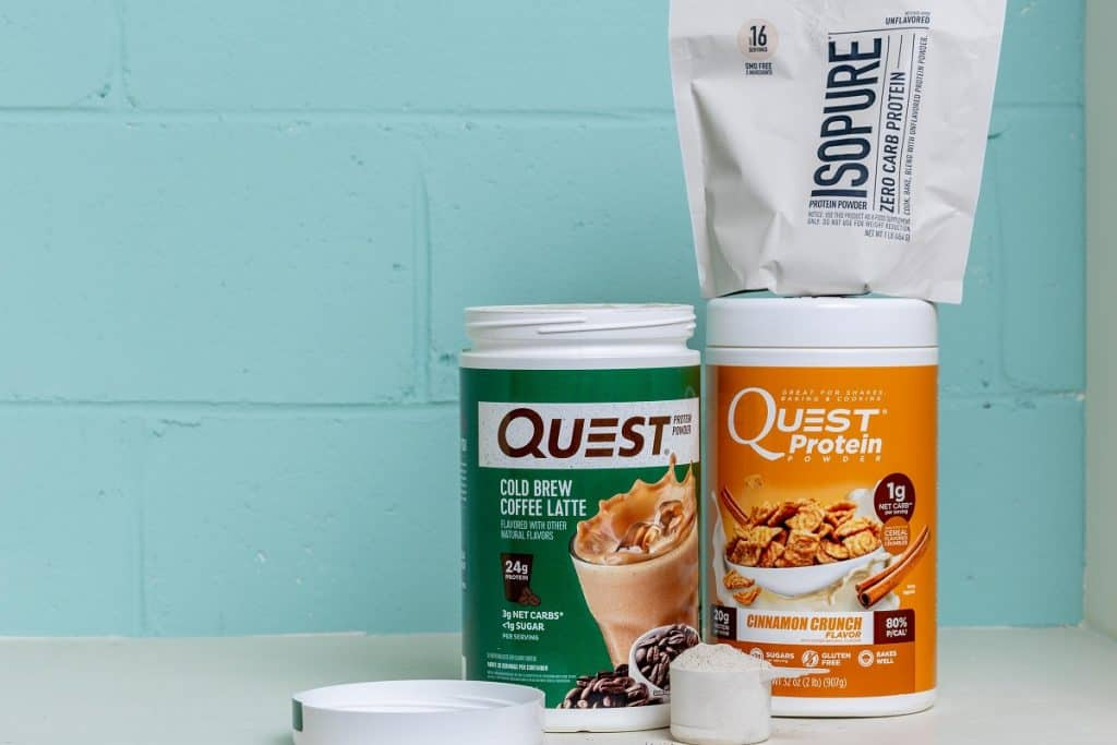 Two canisters of quest and one of isopure protein powders with a scoop of protein sitting in front of them.